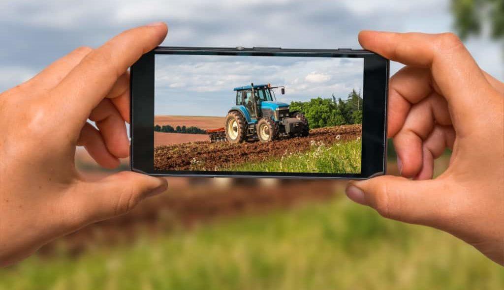 Agricultor tirando foto pelo celular de um trator para vender