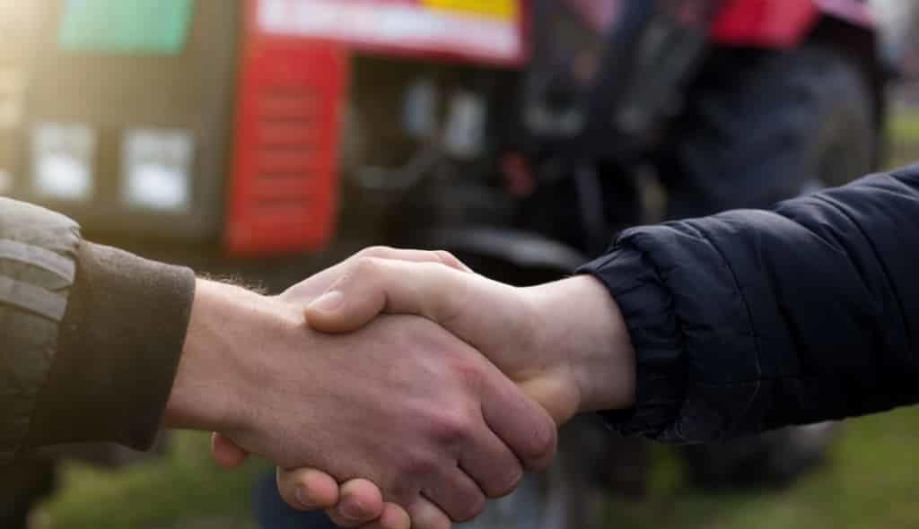 fazendeiros dando as mãos com trator ao fundo