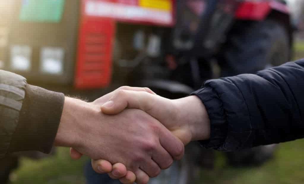 Agricultores dando as mãos com trator ao fundo