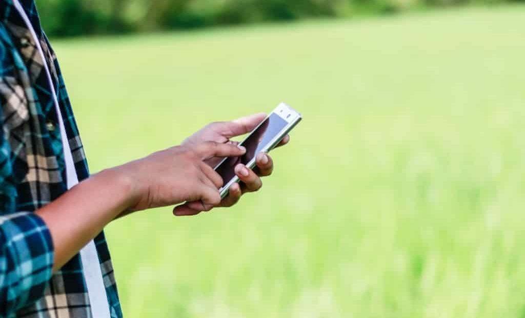 homem com celular no campo