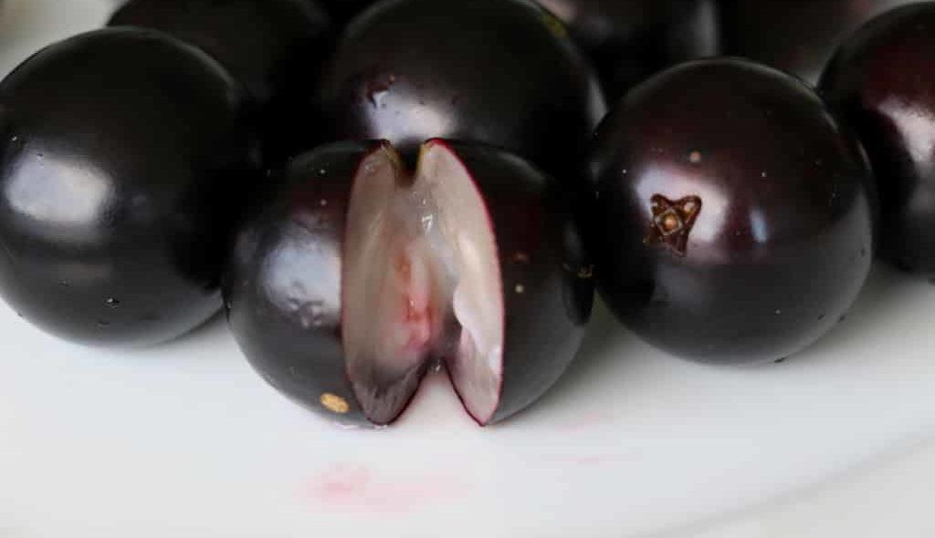 Frutas Jabuticabas com uma cortada ao meio mostrando a polpa