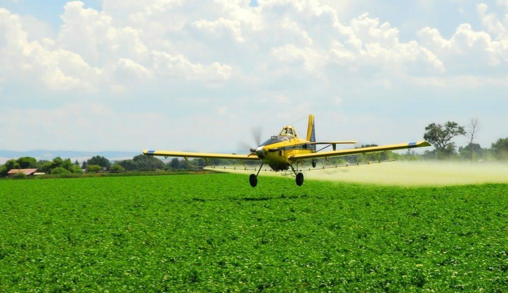 Avião agrícola voando baixo e pulverizando a lavoura