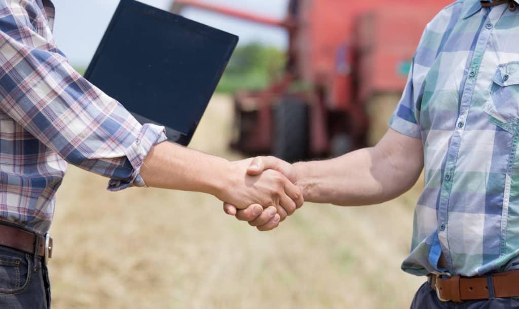 produtores dando as mãos com máquinas agrícolas ao fundo