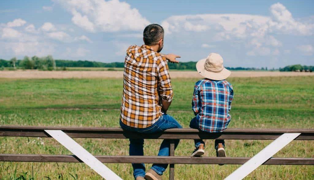 pai e filho sentados de costas na cerca observando a fazenda
