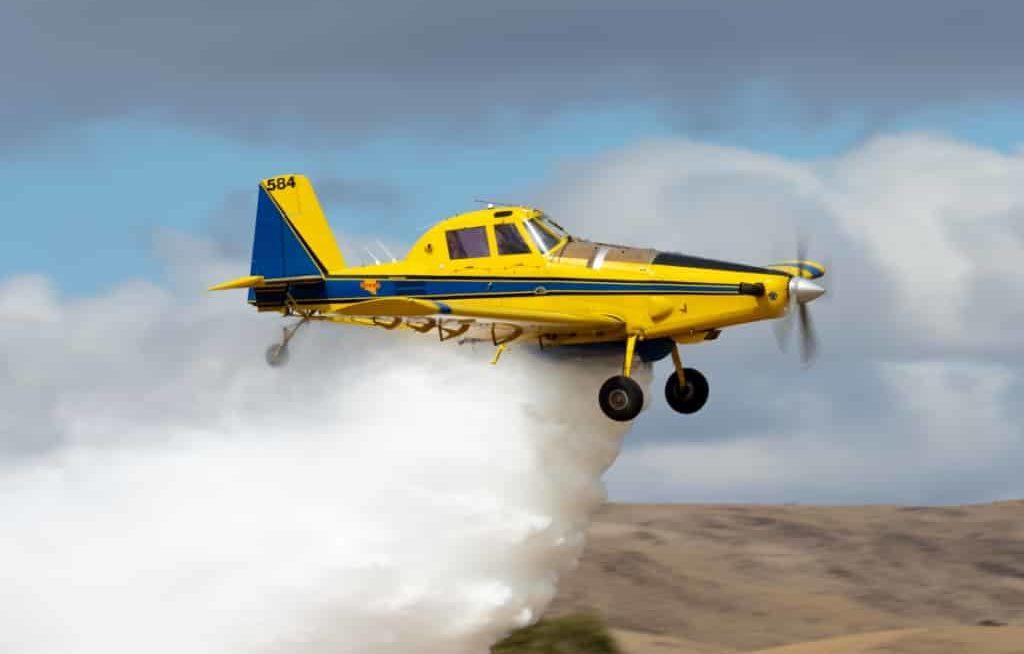 Avião agrícola amarelo pulverizando