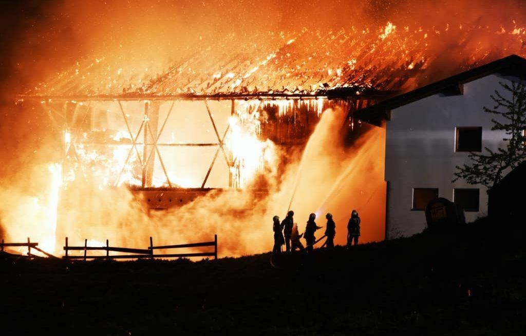 Incêndio em galpão de fazenda e bombeiros apagando o fogo