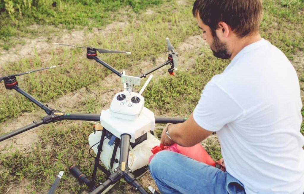 Homem abastecendo drone no chão