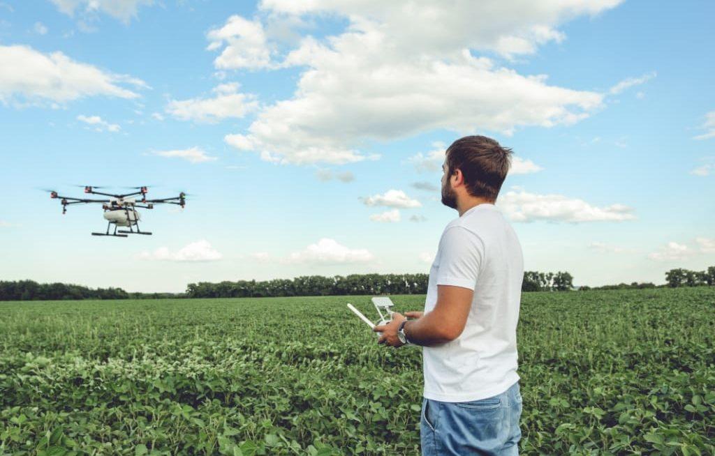 Homem pilotando drone pulverizador em cima de lavoura