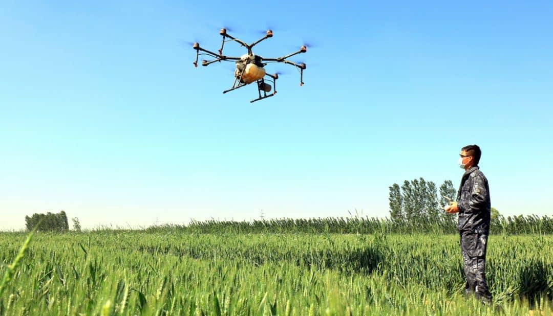 Homem operando drone na pulverização de lavoura.