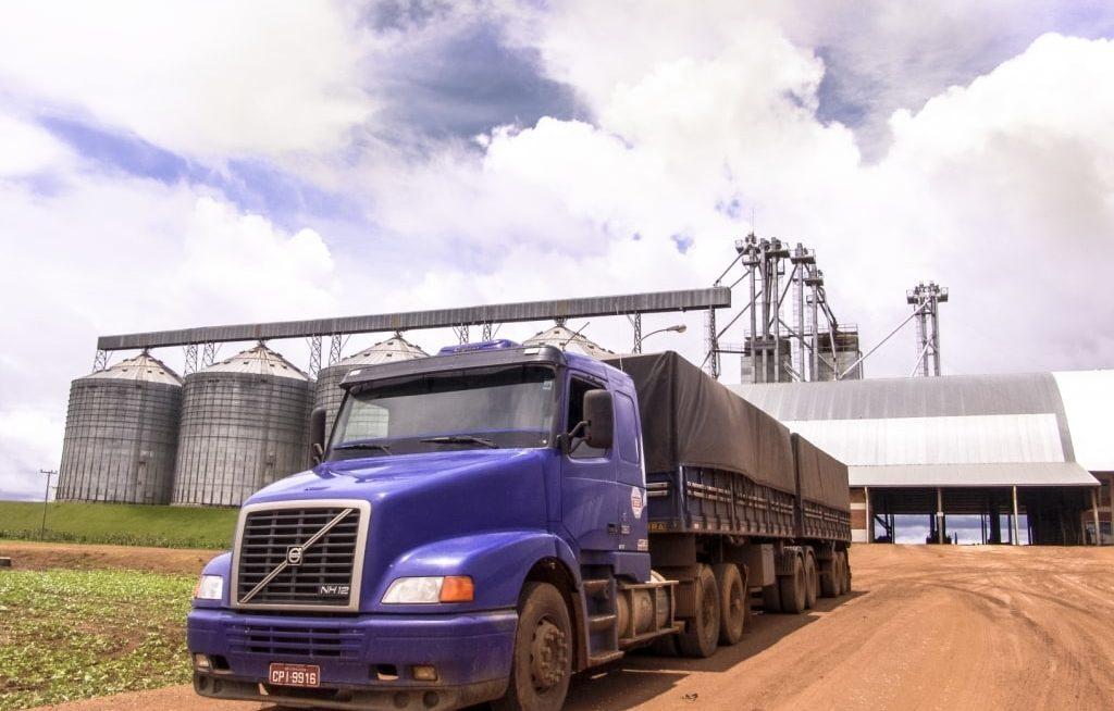 Caminhão graneleiro em frente um silo