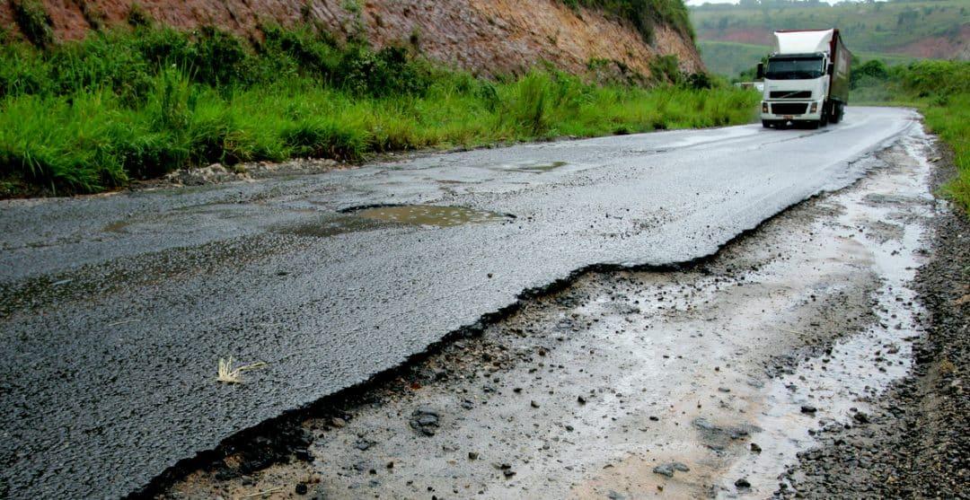 Buracos em rodovia com carreta ao fundo