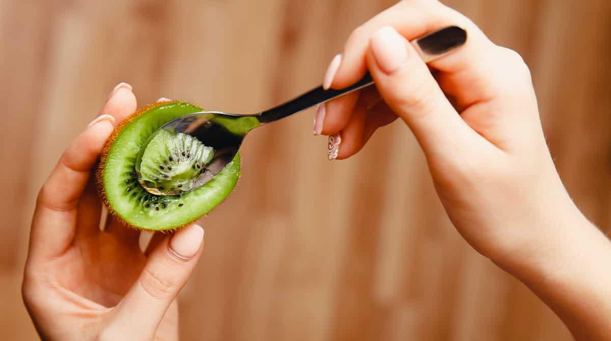 Mulher comendo kiwi com colher, benefícios.