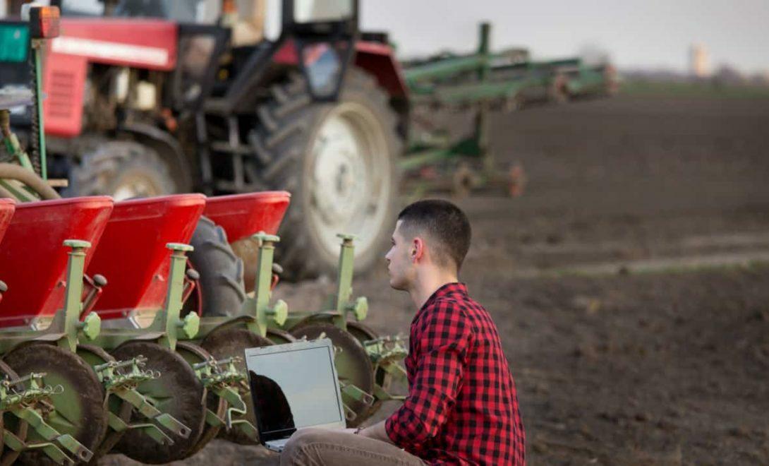 Agricultor com notebook analisa dados das produção agrícola