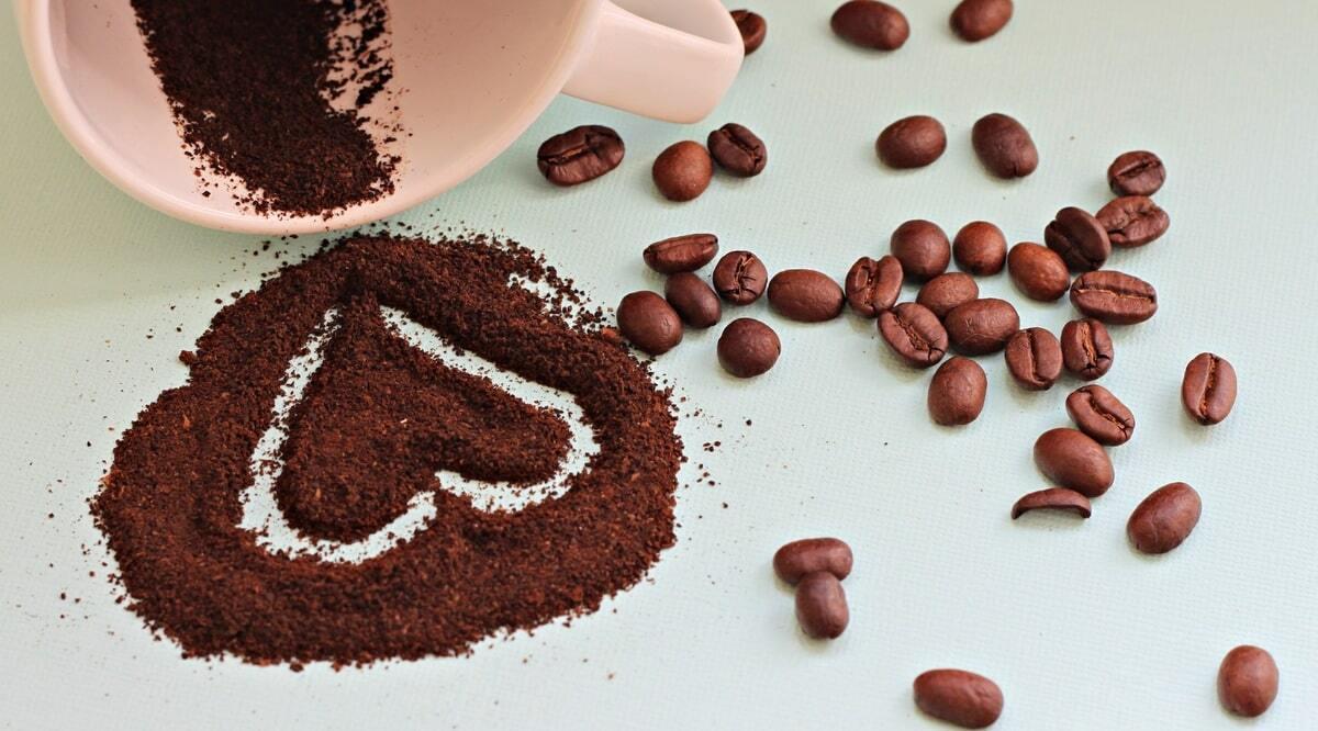 Café em grãos e moído, em forma de coração, indicando benefícios à saúde