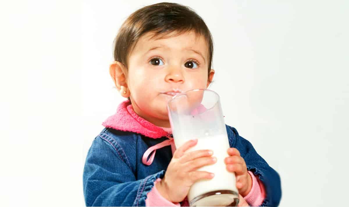 Criança tomando leite no copo