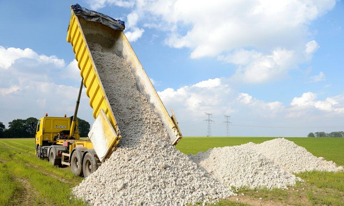 Carreta descarregando calcário em propriedade rural