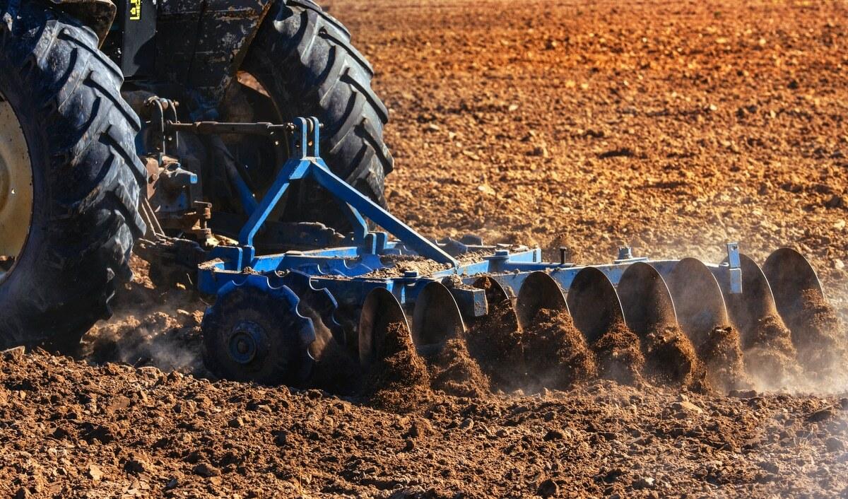 Implemento agrícola, puxado por trator, preparando o solo