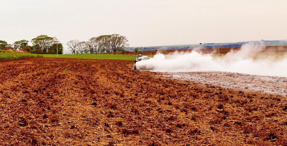 Trator realiza calagem em área preparada para plantio